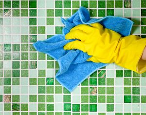 Why You Need Commercial Contract Cleaning UK for Office Tile and Grout - Hand in yellow protective glove cleaning mosaic wall