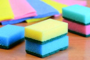 Colorful sponge and rags for cleaning ware and house cleaning. Cleaning sponge with scrub and rags set on a wooden table. Closeup. Contract Cleaning Services in London