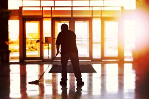 Janitor mopping an office floor, shallow focus, tilt shift image. Holiday periods are a good opportunity for floor care and big cleaning Professional Contract Cleaners in London