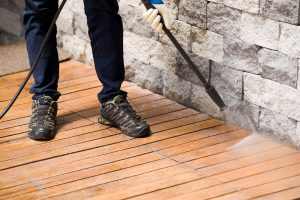 Close up of a man cleaning terrace with a power washer - high water pressure cleaner on wooden terrace surface. Professional builders clean in London by Purgo Supply Services
